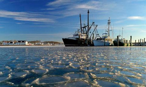 A fishing boat on top of rippled ice water